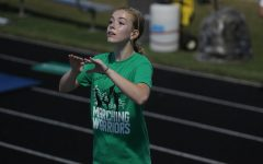 Drum Major Kaitlyn Dirr directs the Marching Warriors as they help cheer on the Weddington High School football team.